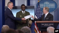 White House press secretary Sean Spicer, right, holds up a check during the daily briefing with Interior Secretary Ryan Zinke, left, and Harpers Ferry National Historic Park Superintendent Tyrone Brandyburg, center, at the White House in Washington, Monda