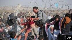 지난 6월 터키 남동부 아크카케일 국경 지역에서 시리아 난민들이 철조망을 사이로 국경을 넘고 있다.