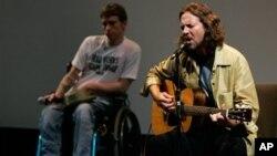 Əlil arabasında oturmuş Tomas Yanq musiqiçi Eddie Vedder-i dinləyir.