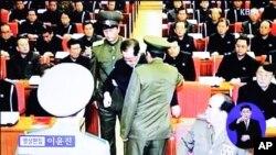 Imágenes de la televisión norcorena muestran al tío Jang siendo escoltado por uniformados de una reunión del politburó del Partido de los Trabajadores.