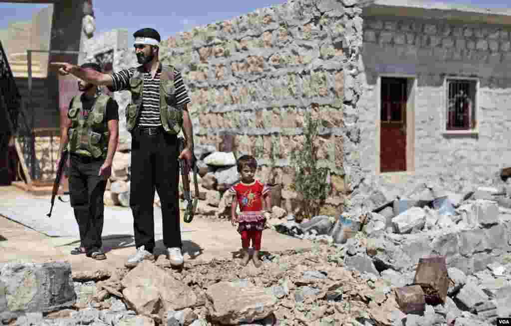 A Syrian child stands next to rebel fighters checking a house that was damaged in bombing by government forces in Marea, on the outskirts of Aleppo, Syria, September 4, 2012.