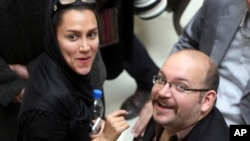 FILE - Jason Rezaian, an Iranian-American correspondent for The Washington Post, and his wife Yeganeh Salehi, an Iranian correspondent for Abu Dhabi-based newspaper The National, attend a presidential campaign of President Hassan Rouhani in Tehran, April 11, 2013.