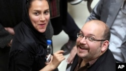 File - Jason Rezaian (R), an Iranian-American correspondent for The Washington Post, and his wife Yeganeh Salehi, an Iranian correspondent for the Abu Dhabi-based The National, attend a presidential campaign of President Hassan Rouhani in Tehran, Iran.