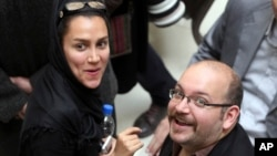 FILE - Jason Rezaian (R), an Iranian-American correspondent for The Washington Post, and his wife Yeganeh Salehi, an Iranian correspondent for the Abu Dhabi-based newspaper The National, attend a presidential campaign of President Hassan Rouhani in Tehran, Apr. 11, 2013.