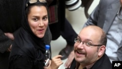 FILE - Jason Rezaian, an Iranian-American correspondent for The Washington Post, and his wife Yeganeh Salehi, attend a presidential campaign of President Hassan Rouhani in Tehran, April 11, 2013.