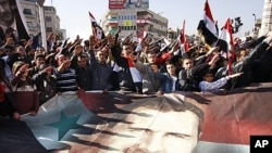 Syrians hold a large poster depicting Syria's President Bashar Assad during a rally in Damascus, Syria. Syria signed an Arab League initiative Monday that will allow Arab observers into the country as part of peace deal that aims to end the nation's incre
