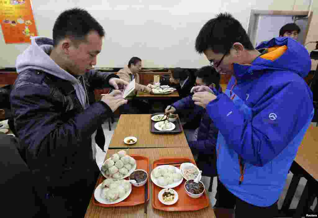 Diners take pictures of similar steamed buns that Chinese President Xi Jinping ate at the Qing-Feng steamed buns restaurant in Beijing. Xi showed off the common touch on Dec. 28, 2013, with a surprise visit to a steamed bun restaurant in Beijing where he paid for his food and happily chatted to surprised customers.