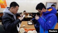 """在北京庆丰包子铺,食客们在品尝习近平""""亲民""""吃过的包子之前用手机拍照。"""