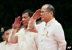 New Philippine President Rodrigo Duterte, left, and outgoing President Benigno Aquino III salute during inauguration ceremony Thursday, June 30, 2016.