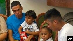 En esta imagen tomada de video, Javier Garrido Martínez (izquierda) y Alan García (derecha), dan una conferencia de prensa en Nueva York luego de haber sido reunidos con sus hijos. Julio, 2018.