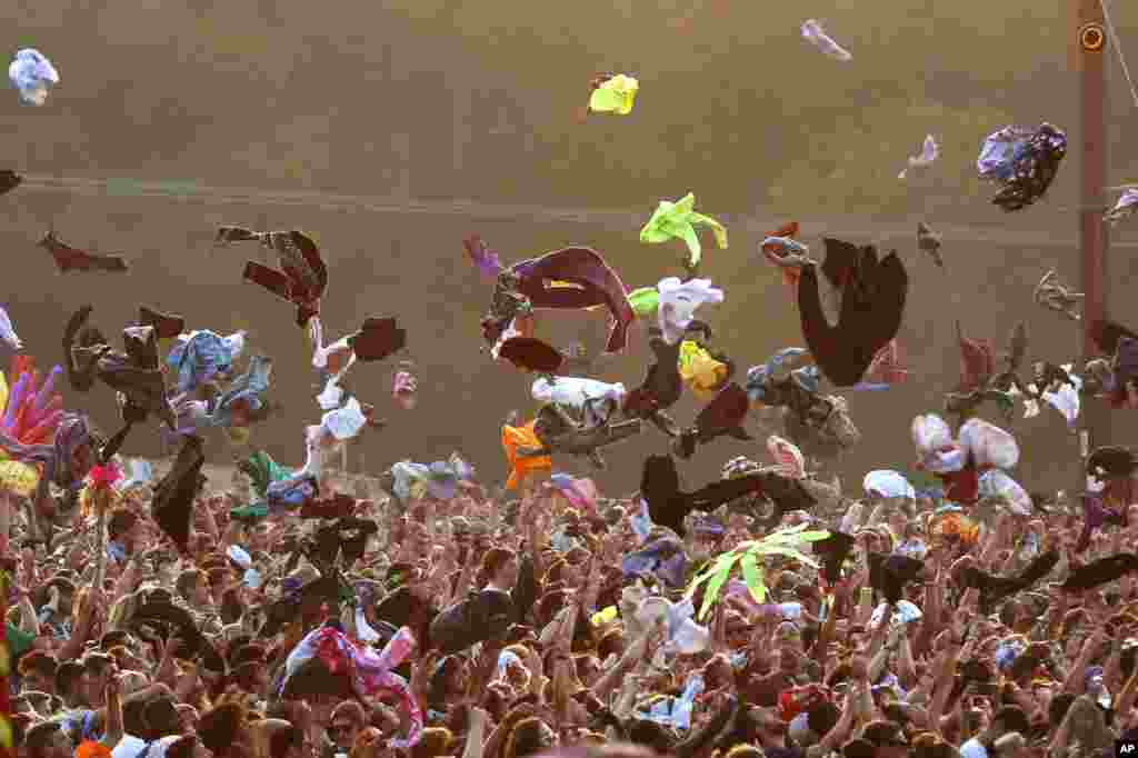 Festival goers throw their t-shirts in the air at the request of performer Major Lazer, at Bestival, held at Robin Hill Adventure Park, Isle of Wight, England, Sept. 7, 2014.