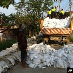 Thai Flood Volunteers Unload Sandbags in Front of Flooded Temple at North Edge of Bangkok
