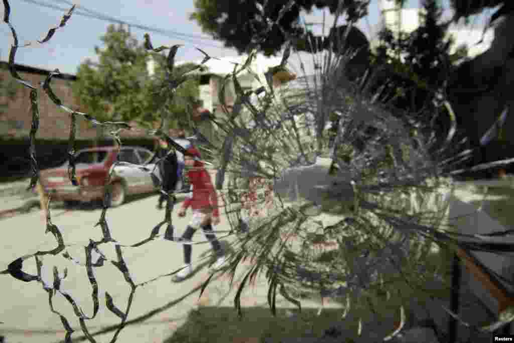 A girl is pictured through a broken window after clashes at Ain al-Hilweh Palestinian refugee camp near the port city of Sidon in south Lebanon. Ten people were wounded and one killed during clashes between the Fatah movement and radical Islamists that started on March 11, 2013.