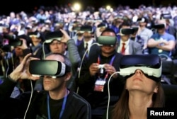 FILE - People wear Samsung Gear VR devices as they attend the launching ceremony of the new Samsung S7 and S7 edge smartphones during the Mobile World Congress in Barcelona, Spain, Feb. 21, 2016.