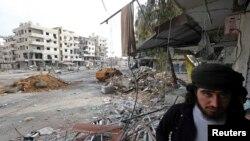 Một chiến binh phe nổi dậy Syria đi trong khu phố bị tàn phá