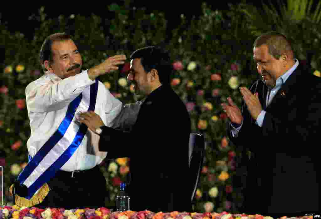 Mr. Ahmadinejad congratulates Nicaragua's President Daniel Ortega, who was sworn in for his second term as president on January 10, 2012. Venezuela's President Hugo Chavez claps on the right. (Reuters)
