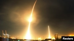 FILE - A long exposure photograph shows the SpaceX Falcon 9 lifting off (L) from its launch pad and then returning to a landing zone (R) at the Cape Canaveral Air Force Station.