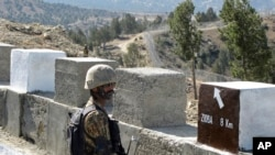 FILE - A Pakistani soldier stands guard at a newly erected fence between Pakistan and Afghanistan at Angore Adda, Pakistan, Oct. 18, 2017.