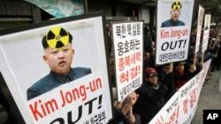 Người Hàn Quốc cầm biểu ngữ với hàng chữ 'hãy lật đổ các nhóm ủng hộ Triều Tiên' trong cuộc biểu tình phản đối việc Triều Tiên có thể tiến hành vụ thử hạt nhân thứ ba tại Seoul.