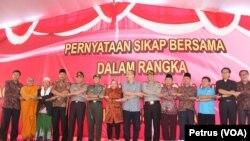 Para pemuka agama dan Forum Komunikasi Pimpinan Daerah Kota Surabaya bergandengan tangan usai membacakan pernayataan sikap bersama untuk menjaga perdamaian di Surabaya, di halaman Tugu Pahlawan Surabaya, 24 Juli 2015 (Foto: VOA/Petrus)