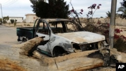 A burned truck is seen outside al-Rawdah mosque in Bir al-Abed, northern Sinai, Egypt, a day after attackers killed hundreds of worshippers, Nov. 25, 2017. Friday's assault was Egypt's deadliest attack by Islamic extremists in the country's modern history.