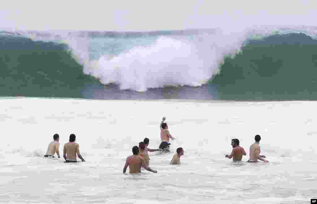 Italy players relax in the breakers of the Atlantic ocean at the soccer Confederations Cup in Rio de Janeiro, Brazil.