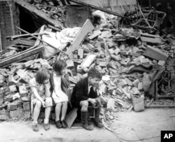 In this photo provided by the U.S. Office of War Information, three children are sitting next to the remains of what was once their home in East London after another night of German bombings, in the early days of the Blitz during World War II, September 1940.