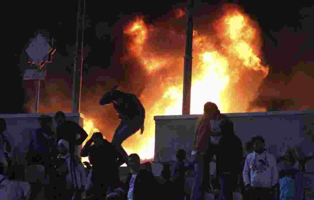 Seorang penggemar sepakbola melarikan diri dari kebakaran di Stadion Kairo di Port Said, Mesir, 1 Februari 2012 ( REUTERS).