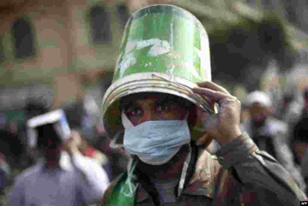 An Egyptian anti-government protester uses a bucket as a helmet during clashes in Cairo's Tahrir square, Egypt, Thursday, Feb. 3, 2011. Protesters and regime supporters skirmished in a second day of rock-throwing battles at a central Cairo square while ne