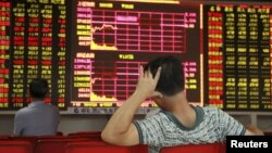 Investors track stock market information in Hiakou, Hianan China. China's stock market has lost 40 percent in value since June. Other markets around the world have had sharp gains and losses in recent weeks.