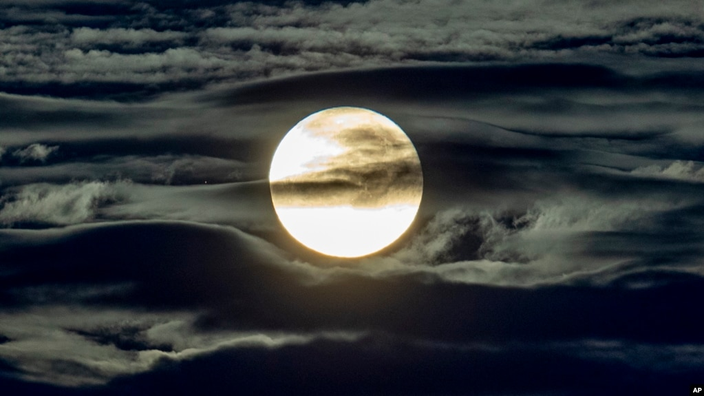 The full moon shines surrounded by clouds in the outskirts of Frankfurt, Germany, early Wednesday, Sept. 2, 2020.