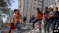 Palestinci evakuiraju djevojčicu iz ruševina uništene zgrade u stambenoj četvrti Rimal grada Gaze 16. maja 2021. godine,