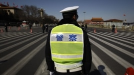 Chinese police wait for the arrival of delegates for a session of the National People's Congress outside the Great Hall of the People in Beijing, China, March 11, 2012.