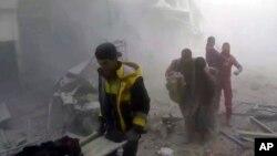 Hình ảnh chụp từ video công bố hôm thứ Bảy, 24 tháng 2, 2018 bởi nhóm Dân phòng Syria, còn được biết tới với cái tên lực lượng Mũ Trắng, cho thấy các thành viên của nhóm này giúp đỡ cư dân trong một vụ không kích và pháo kích của chính phủ Syria ở khu ngoại ô Ghouta của thủ đô Damascus.