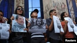 FILE - Protesters hold pictures during a protest in support of imprisoned activists at a Cairo jail.