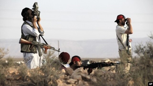Rebel fighters patrol in the desert south of the Libyan rebel-held town of Chakchuk in the Western Mountains, some 160 km (99.4 miles) southwest of Tripoli, June 4, 2011.