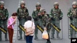 Warga lokal menyerahkan minuman dingin kepada tentara yang berjaga-jaga mencegah demonstrasi anti kudeta di Monumen Kemenangan, di Bangkok, Thailand, 29/5/2014.