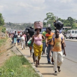 Residents of Abobo district, a suburb of Abidjan, flee the quarter carrying their luggage on their heads on February 25, 2011