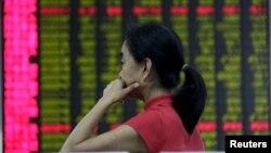 Nhà đầu tư nhìn vào bảng điện tử hiển thị thông tin chứng khoán tại một Trung tâm Môi giới Chứng khoán ở Bắc Kinh, ngày 26/8/2015.