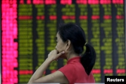 An investor looks at an electronic board showing stock information at a brokerage house in Beijing, Aug. 26, 2015.