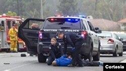 Un agente de la policía de Whittier arresta a uno de los sospechosos del tiroteo ocurrido el lunes por la mañana en esta localidad.