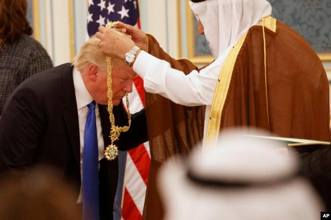 沙特國王薩勒曼給美國總統川普佩戴普阿卜杜勒阿齊茲‧沙特國王金質獎章。