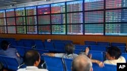 Các nhà đầu tư và môi giới theo dõi thông tin chứng khoán ở sàn chứng khoán ACB tại Hà Nội.