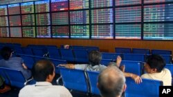 In this photo taken Monday, Sept. 10, 2012, investors and brokers are seen at the Asia Commercial Bank (ACB) Stock Exchange in Hanoi, Vietnam.