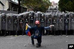 مردی در برابر پلیس که مانع یک راهپیمایی به دعوت خوان گوایدو، رهبر مخالفان، در کاراکاس در ونزوئلا، شده زانو زده است. ۱۰ مارس ۲۰۲۰