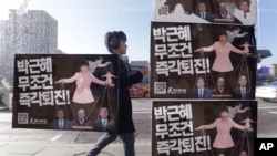 A man walks by a bus stop displayed with posters depicting impeached South Korea's President Park Geun-hye in pink manipulating three of her aides while she is also manipulated as a marionette by her jailed confidante Choi Soon-sil, seen above Park's left shoulder, in Seoul, South Korea, Dec. 27, 2016.
