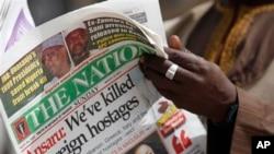 Seorang pria membaca koran lokal yang memuat pernyataan kelompok Ansaru bahwa kelompoknya telah membunuh tujuh sandera asing sebagai berita utama di halaman depannya, di Kano, Nigeria (10/3).
