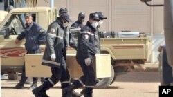 Des pompiers algériens transportant de cercueils a In Amenas, Algérie, 21 janvier, 2013.