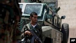 Seorang tentara Yaman tengah berjaga di sebuah pos penjagaan di jalanan menuju Kedutaan AS dan Inggris di Sanaa, Yaman, 10 Agustus 2013 (Foto: dok). Tersangka militan al-Qaida dilaporkan melancarkan tiga serangan serentak di selatan Yaman, menewaskan 56 polisi dan tentara, Jumat (20/9).