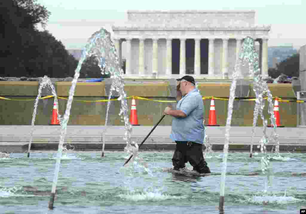 With the Lincoln Memorial in the distance, a worker cleans the fountain at the World War II Memorial in Washington, D.C., Oct. 17, 2013.